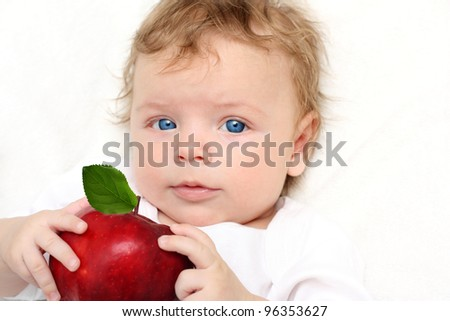 Baby boy on white blanket with apple smiling. - stock photo