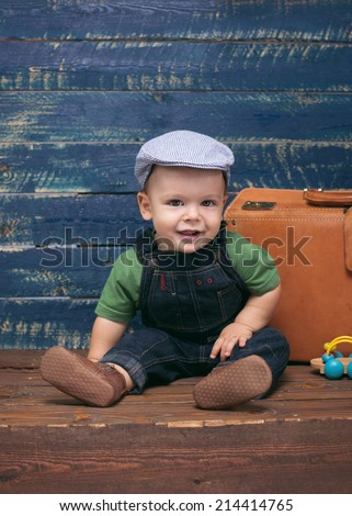 Baby boy on wooden background, vintage setup - stock photo