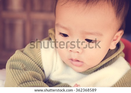 Baby boy on wooden background, vintage stley