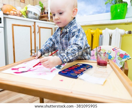 Baby boy painting with watercolors. Small caucasian child playing in home with paint and brush - stock photo