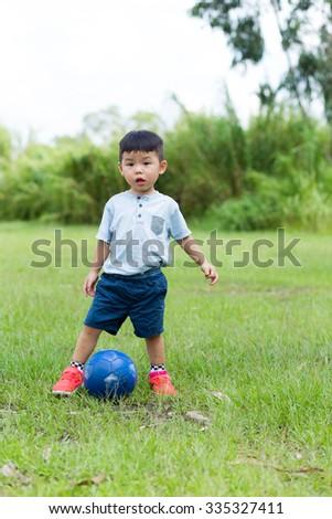 Baby boy play soccer ball at outdoor - stock photo