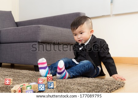Baby boy play toy block at home - stock photo