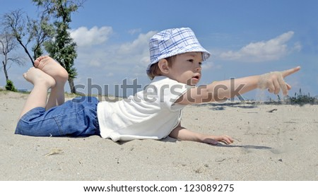 Baby boy playing in sand on beach - stock photo