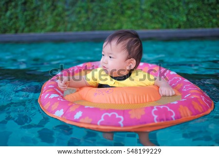Baby boy playing in the outdoor swimming pool