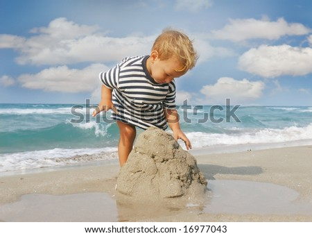 baby boy playing on beach - stock photo