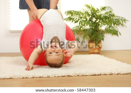 Baby boy playing on big red ball - stock photo
