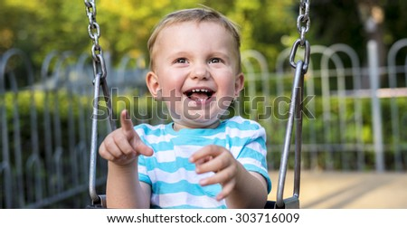 Baby boy playing on the swing in the park - stock photo