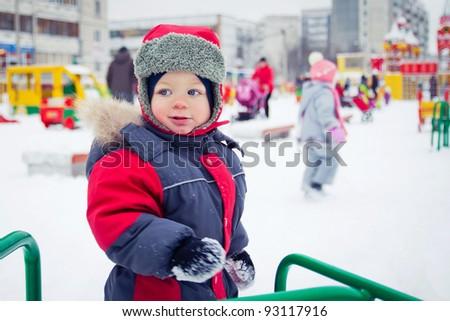 baby boy playing  on winter playground - stock photo