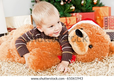 Baby boy playing with a big teddy bear at Christmas