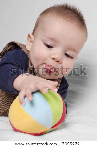 Baby boy playing with a toy on a bed at home - stock photo