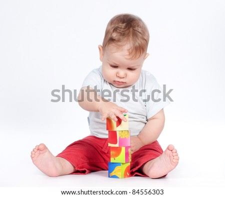 baby boy playing with blocks on white background