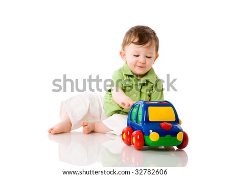 Baby boy playing with colorful car toy isolated on white - stock photo