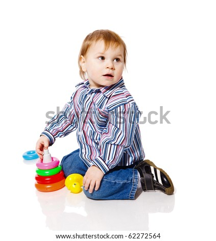 Baby boy playing with colorful pyramid toy isolated on white