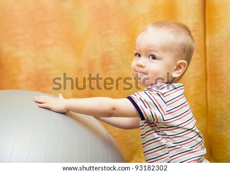 baby boy playing with fit ball in nursery - stock photo