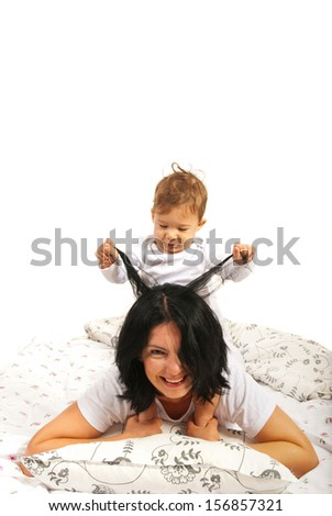 Baby boy playing with her mother hair and having fun in bed - stock photo