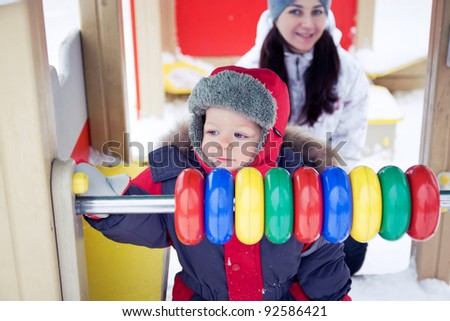 baby boy playing with his mother on a winter playground - stock photo