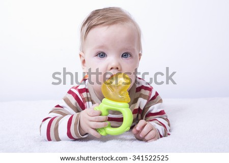 Baby boy playing with teether, chewing toy - stock photo