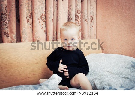 Baby boy posing on parents' bed in bedroom - stock photo
