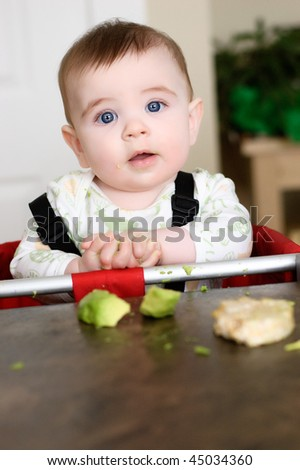 Baby boy reaching for ricecake and avocado to eat