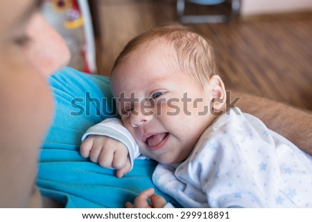 Baby boy resting on his dads chest - stock photo