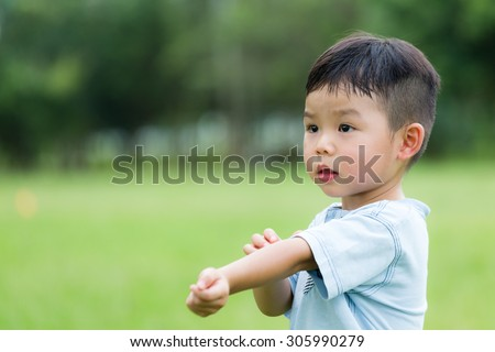 Baby boy scratching his arm - stock photo