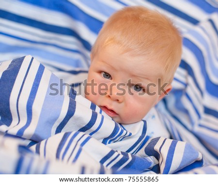 baby boy seven months  portrait in blue sheets - stock photo