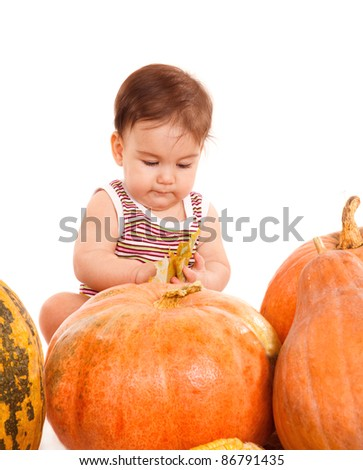 Baby boy sitting among large ripe pumpkins