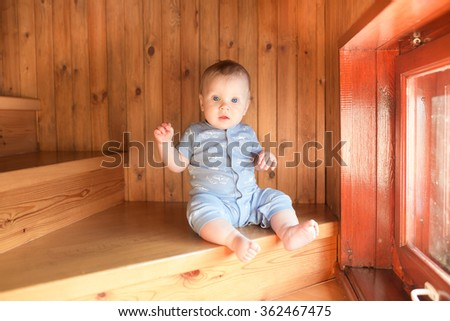 Baby boy sitting and climbing up stairs. - stock photo