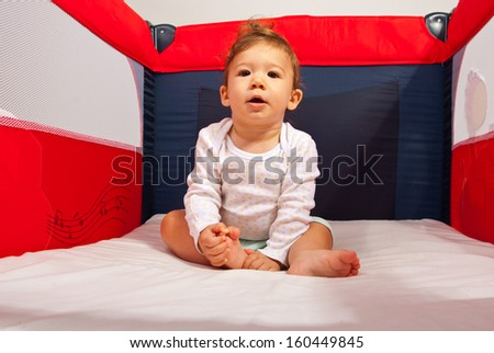 Baby boy sitting down in plypen and looking camera - stock photo