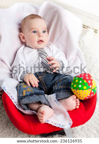Baby boy sitting in car seat - stock photo