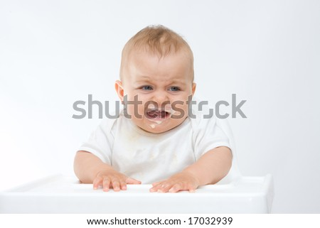 baby boy sitting in highchair and crying - stock photo
