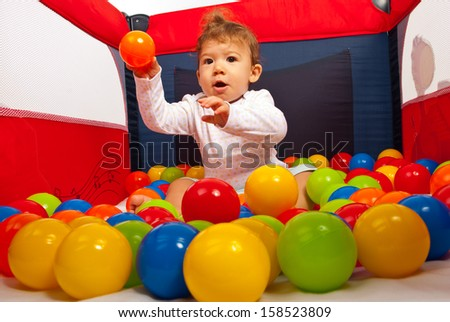 Baby boy sitting in playpen with colorful balls and throwing a orange ball - stock photo