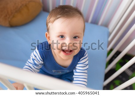 Baby boy sitting in the crib - stock photo