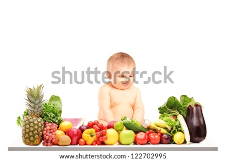 Baby boy sitting on a table full of different fruits and vegetables isolated against white background - stock photo