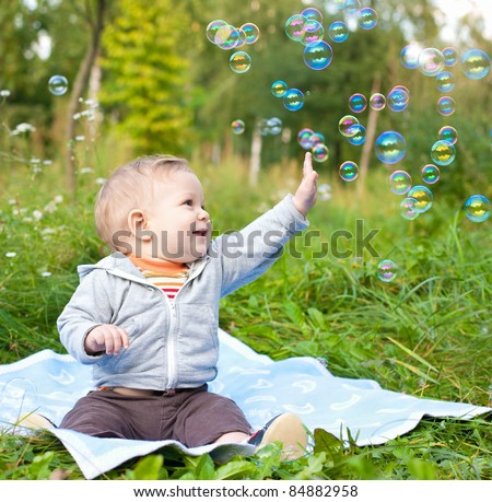 baby boy sitting on green grass outdoor playing with soap bubbles - stock photo