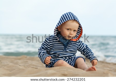 baby boy sitting on sand beach, playing with sand, dressed in marine clothes, sailor kid, sea with waves background, Bibione, Italy - stock photo