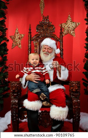 Baby boy sitting on Santa's lap at Christmas time. - stock photo