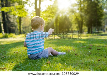 Baby boy sitting on the grass in the city park and pointing towards - stock photo