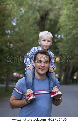 Baby boy sitting on the shoulders of a young father in summer park - stock photo