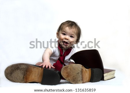 Baby boy sitting with his preacher's dad's shoes and bible (Concept:: I want to be just like you dad) - stock photo