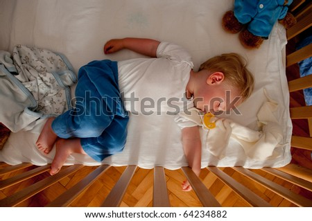 Baby boy sleeping in his bed - stock photo