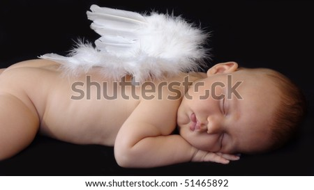 Baby boy sleeping with angel wings on his back - stock photo