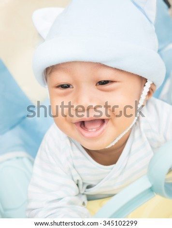 Baby boy smiling and showing his first teeth