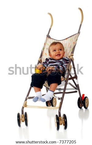 Baby boy smiling up from an umbrella stroller.