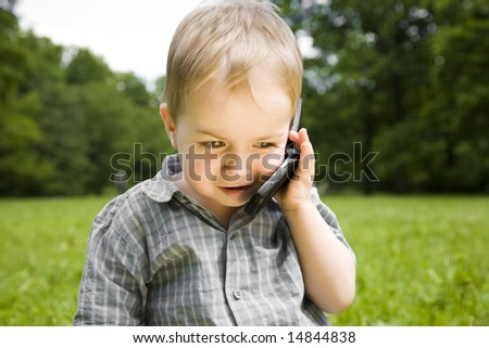 Baby Boy Speaking By Phone Outdoors - stock photo