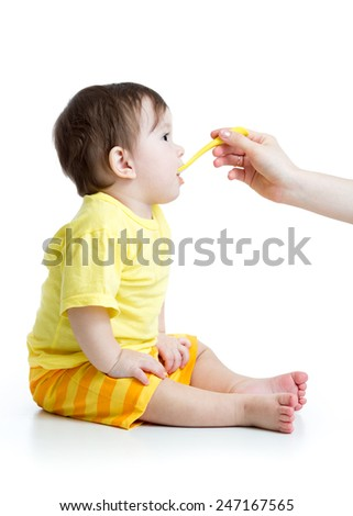 baby boy spoon feeding isolated on white - stock photo