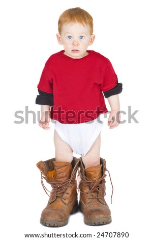 Baby boy standing in an adult pair of work boots - stock photo
