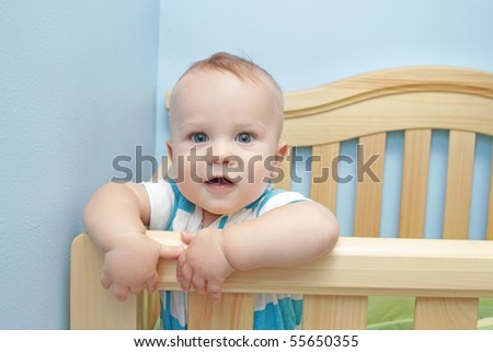 Baby boy standing in crib, smiling - stock photo