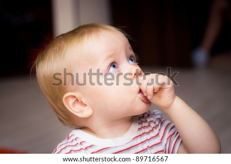Baby boy sucking his thumb at home - stock photo