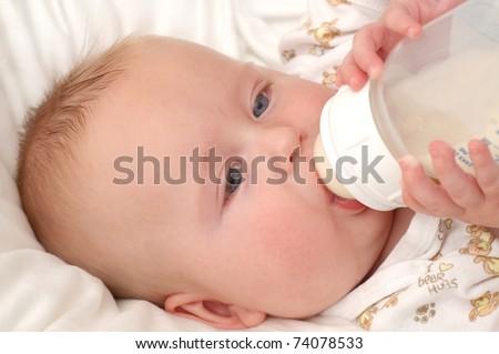 Baby boy sucking on his bottle - stock photo